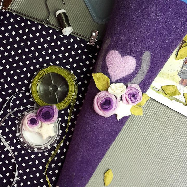 Violette Schultüte gefilzt. Mit Hufeisen, Filzrosen und grünem Chiffonband.